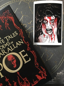Photo of art print beside the collected works of Edgar Allan Poe